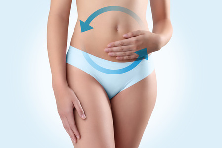 digestion: woman hands on belly with blue arrow Stock Photo