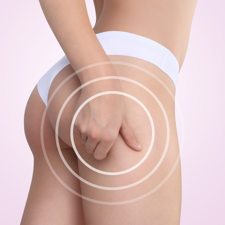 Woman pinches her thigh to control cellulite on pink background photo