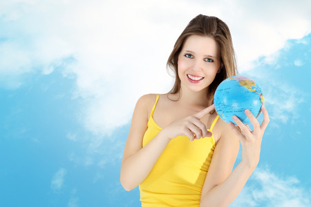 smiling girl pointing to map of the world photo