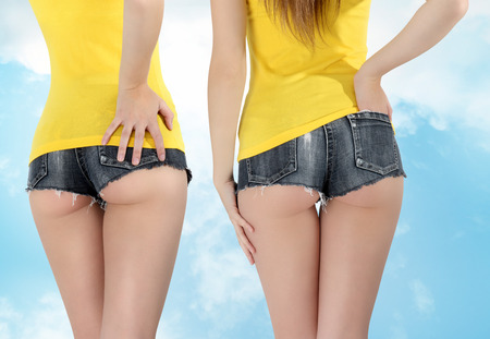 ass woman wearing a short jeans shorts with yellow tank top photo