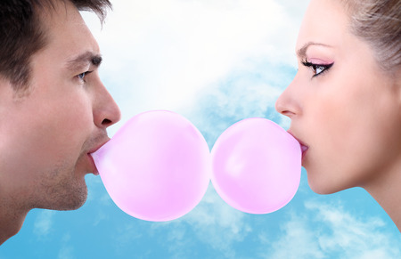 cheerful young couple playing with chewing gum photo