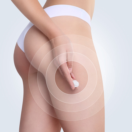 Female applying cosmetic cream from cellulite on the buttocks in white background Stock Photo