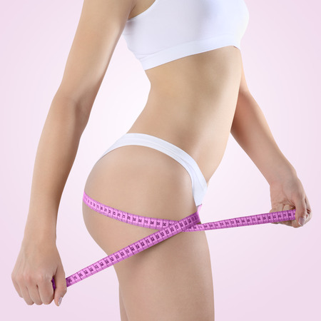 body of woman with diet meter, Isolated on pink background photo