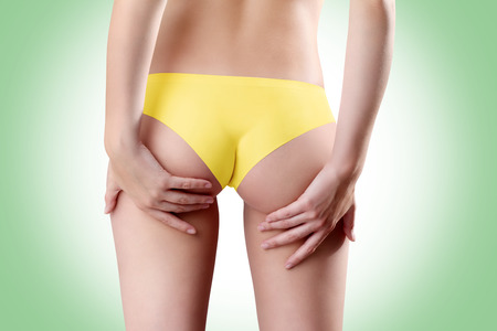 Bum and legs of woman, hands touching the buttocks over green background photo