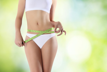 beautiful navel women: belly woman with meter on green background