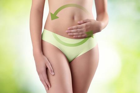 abdomen plano: manos de la mujer en el vientre con la flecha verde