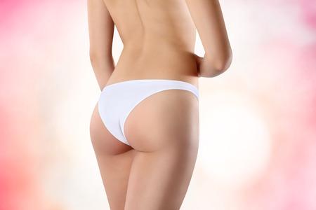 nalga: Hermoso cuerpo de mujer exponiendo parte inferior y trasera, aislado en el fondo de color rosa Foto de archivo