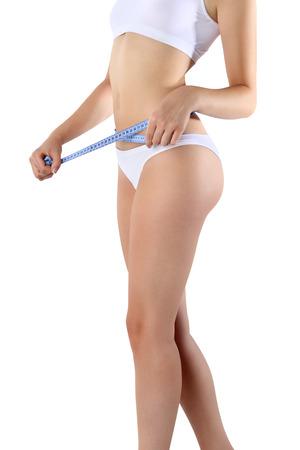허리의 잘룩 한 선: 여자 흰색 배경에 허리 근처 손으로 파란색 미터를 잡고있다