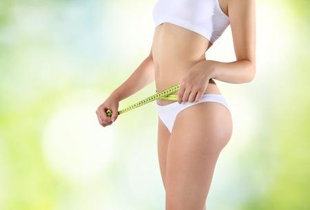 abdomen plano: mujer que sostiene metro verde con las manos cerca de la cintura, en un fondo verde