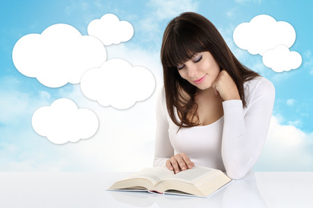 absorbed: girl absorbed in reading a book on background with sky and white clouds