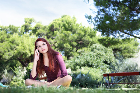 girl sitting in the park with cell phone look up photo