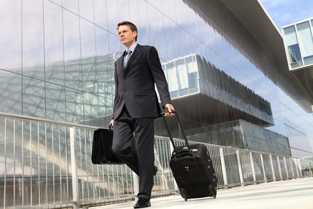 businessman walking with trolley and bag, business travel Stock Photo