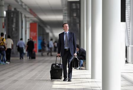 zakenman lopen met trolley door de menigte op een zakenreis