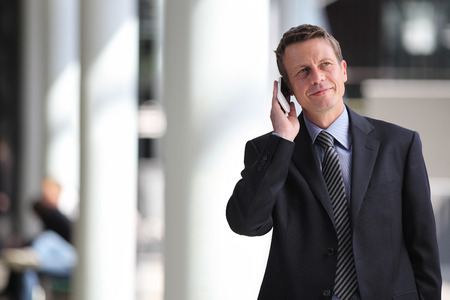 business exhibition: smiling businessman talking on the phone during a business trip Stock Photo