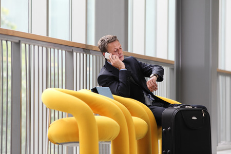 businessman waiting call: businessman sitting talking on the phone, on a business trip