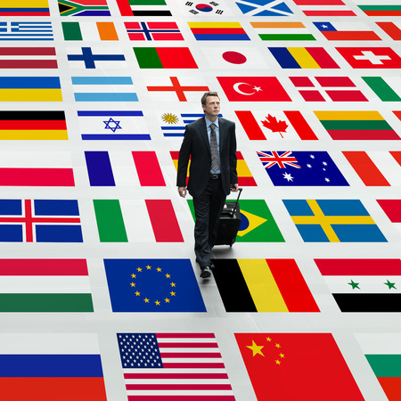 maps globes and flags: business man travels the world, walking on a background of international flags