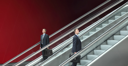 going down: business man going up and down escalators, concept of choice and success Stock Photo