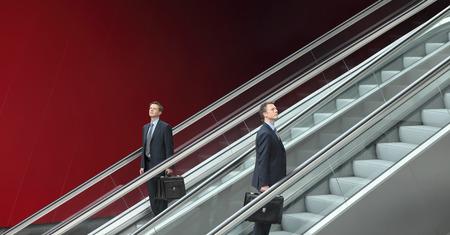 bajando escaleras: hombre de negocios que suben y bajan escaleras mecánicas, el concepto de elección y éxito