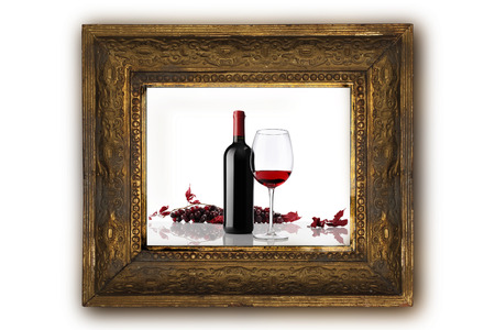 wine bottle with glass and bunch of red grapes on old classic wooden picture frame carved by hand on white background photo