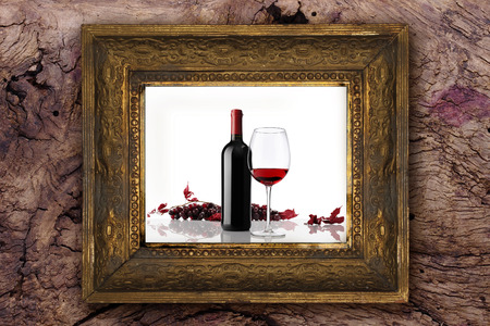 wine bottle with glass and bunch of red grapes on old classic wooden picture frame carved by hand on wood background photo