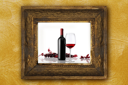wine bottle with glass and bunch of red grapes on old classic wooden picture frame carved by hand on gold wallpaper background photo