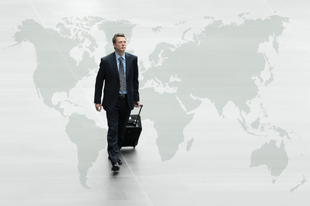 businessman carrying a globe: business man walking on the world map, international travel concept