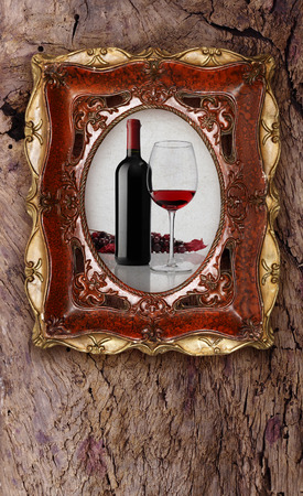 bottle and glass wine in old picture frame on wood background photo