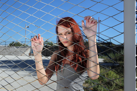 women s fashion: Teen clings to the metal mesh of the playground Stock Photo