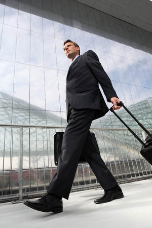 businessman walking with bag and trolley