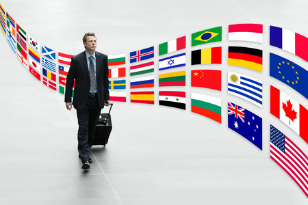 businessman traveling with trolley international flags trip concept Stockfoto