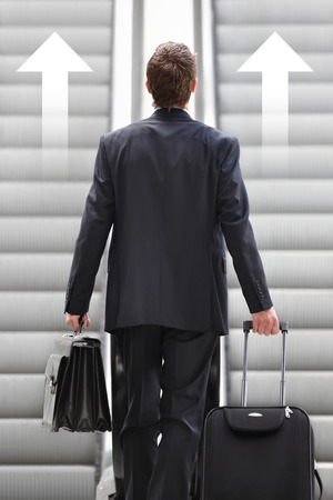 arrive: businessman front escalator with arrows