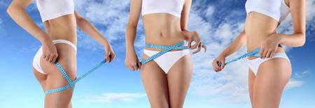 metro de medir: Mujer metros de cinta en las nalgas y vientre Foto de archivo