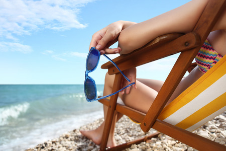 recliner: hands with sunglasses on the beach