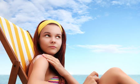 suncare: woman sitting at the beach you put the sunscreen