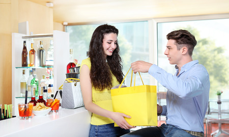 woman s bag: smiling girl receiving a gift from her boyfriend Stock Photo