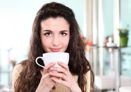 girl smiling in coffee drink with cup in hand photo