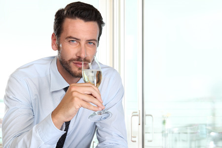 presumptuous: beautiful man drinking champagne with intriguing look and haughty Stock Photo
