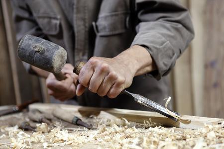 manos de carpintero con un martillo y un cincel en la mesa de trabajo en la carpintería