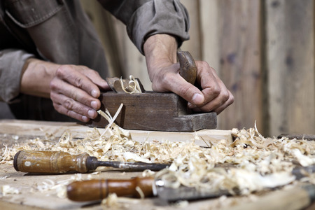 mãos do avião carpinteiro na bancada de carpintaria Foto de archivo
