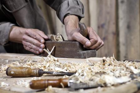 herramientas de carpinteria: manos de avión carpintero en la mesa de trabajo en la carpintería Foto de archivo