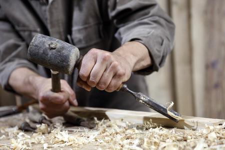 carpintero: manos de carpintero con un martillo y un cincel en la mesa de trabajo en la carpintería