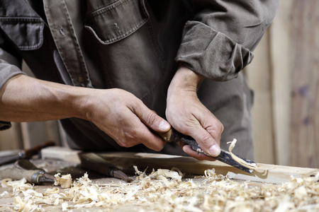 carvings: carpenter with chisel in the hands on the workbench in carpentry