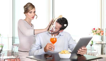 mujer decepcionada: mujer enojada tirando de la torta en la cara al enga�o novio Foto de archivo