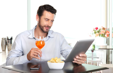cocktail bar: happy man with drink and tablet at the bar