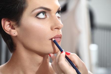 mujer maquillandose: bella modelo haber delineador de labios aplicada por el artista de maquillaje