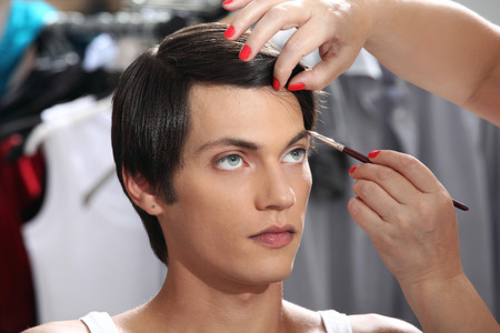 casting: eyebrows with makeup brush, model at mirror in dressing room