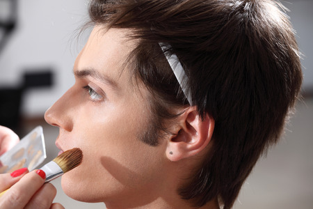 casting: makeup artist applying foundation with a brush, man in the dressing room mirror