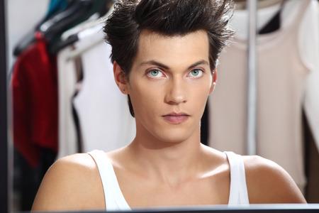hombres gays: retrato de la modelo guapo en el espejo en el vestidor