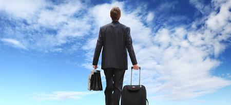 negocios internacionales: hombre de negocios de viaje con carro caminando hacia el cielo Foto de archivo