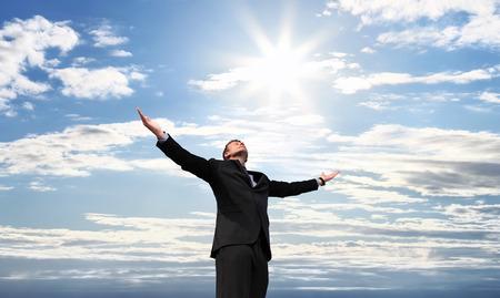 Hombre de negocios en la cima del éxito, los brazos abiertos hacia el cielo Foto de archivo - 43371827